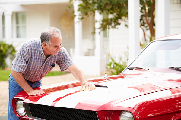 A photo of a man washing his classic car that would benefit from collector car insurance