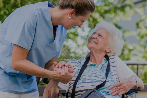A caregiver and an elderly patient - Links to Business Specialty Insurance page