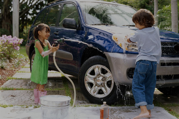 Two kids having fun washing their parents car - Links to Personal Insurance page