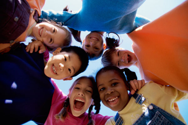 A photo of a group of children all smiling in a circle - Links to Human Services Insurance page